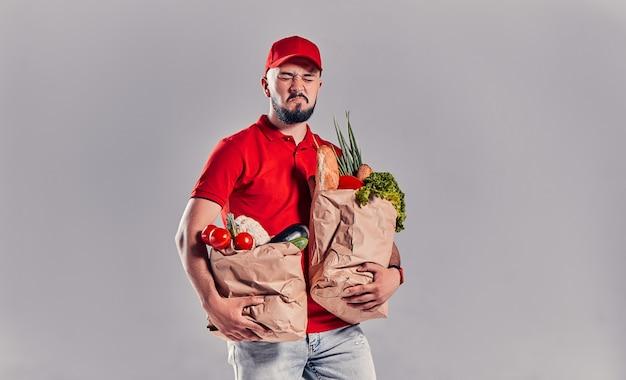 Молодой бородатый курьер в красной футболке и кепке держит в руках два тяжелых мешка с едой. доставка еды на дом.