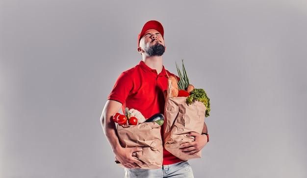 Молодой бородатый курьер в красной футболке и кепке держит два очень тяжелых мешка с едой. доставка еды на дом.