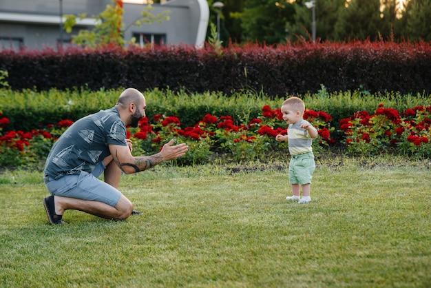 Молодой бородатый отец помогает и учит своего маленького сына делать первые шаги во время заката в парке на траве.