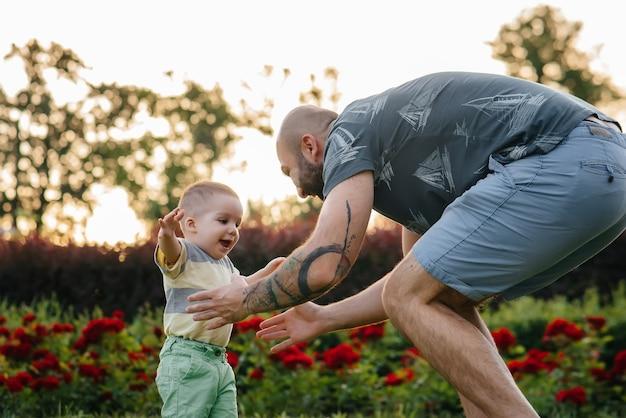 若いひげを生やした父親は、芝生の上の公園で日没時に最初の一歩を踏み出すように彼の幼い息子を助け、教えています。