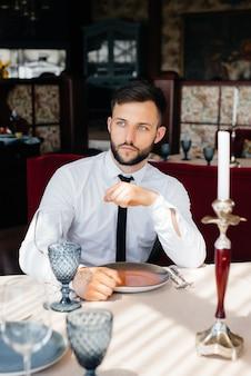 수염을 기른 젊은 남성 사업가가 고급 레스토랑의 테이블에 앉아 주문을 기다리고 있습니다. 케이터링에서 고객 서비스.