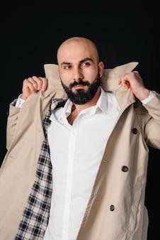 Молодой бородатый мужчина поправляет плащ у черной стены. молодой успешный бизнесмен.