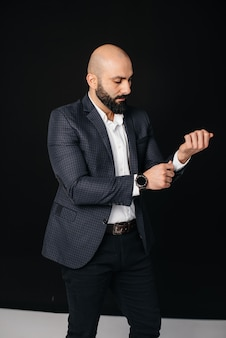 Молодой бородатый мужчина в белой рубашке и куртке стоит у черной стены.