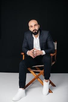 白いシャツとスーツを着た若いひげを生やした男は、黒い背景に座っています。