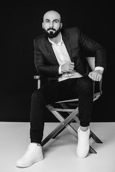 На черной стене сидит молодой бородатый мужчина в белой рубашке и костюме. черное и белое.
