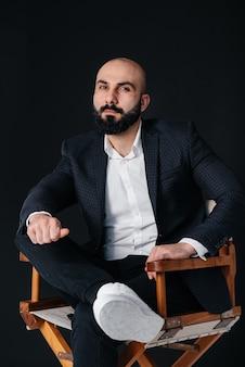 흰 셔츠와 양복을 입은 젊은 수염 난 남자가 검은 벽에 앉아있다.