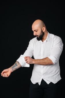 На черной стене стоит молодой бородатый мужчина в белой рубашке и татуировках.