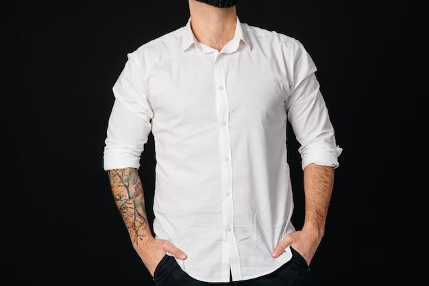 흰 셔츠와 문신에 수염 난 젊은이가 검은 벽에 선다.