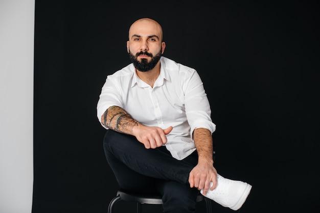 白いシャツを着た若いひげを生やした男は、黒い背景に座っています。