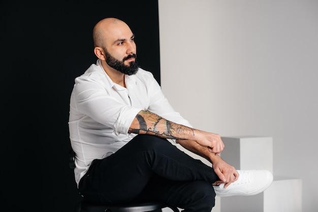 На черной стене сидит молодой бородатый мужчина в белой рубашке.