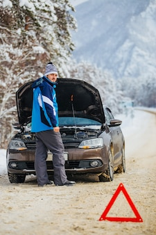 Молодой бородатый мужчина зимой в горах должен был сломать машину, чтобы позвать на помощь по телефону