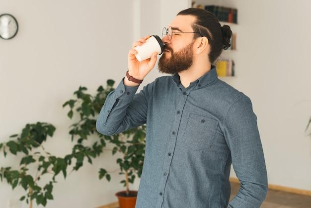 若いひげを生やした男がオフィスで温かい飲み物を飲んでいます