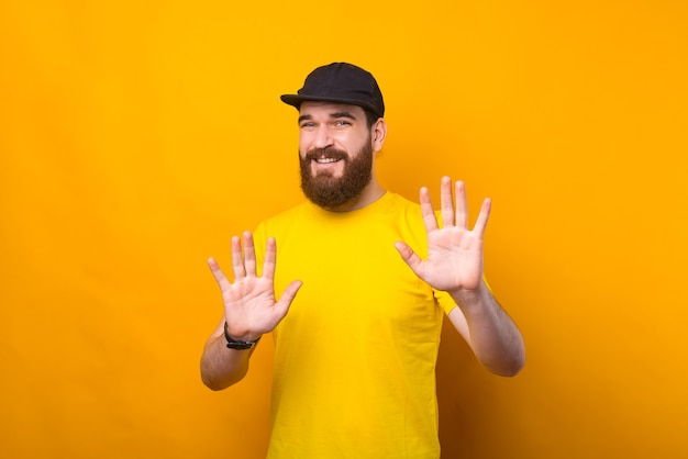 수염 난 젊은이가 정지 신호를 보여주는 노란색 벽 근처에 앉아있다.
