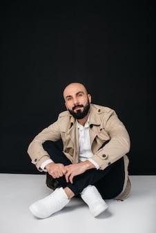 若いひげを生やした男は、黒い背景のレインコートで床に座っています。