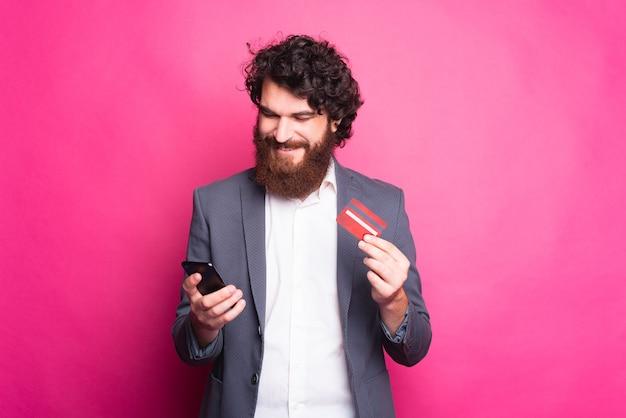 Молодой бородатый мужчина улыбается и смотрит в свой телефон, а в другой руке держит кредитную карту