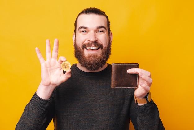 Улыбающийся молодой бородатый мужчина держит биткойн и смотрит в бумажник