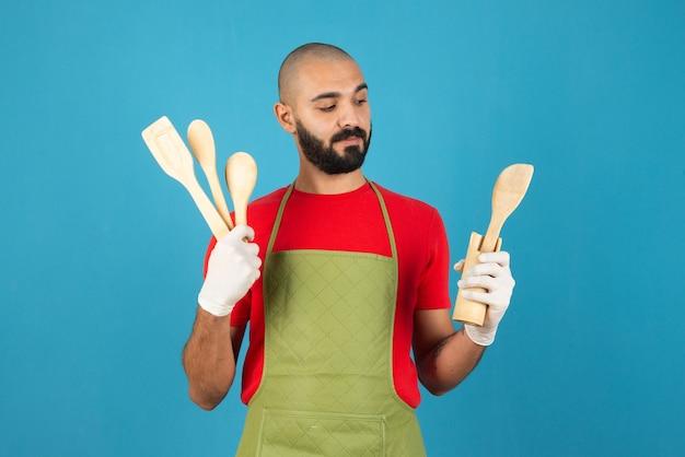 立って台所用品を持っているエプロンを身に着けている若いひげを生やした男。
