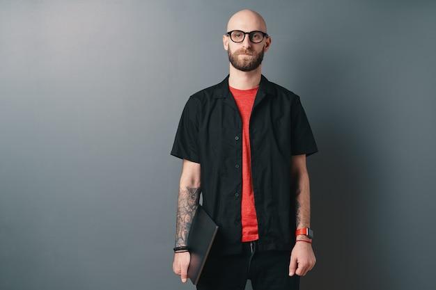 회색에 스튜디오에서 팔 아래 노트북을 들고 안경 젊은 수염 남자