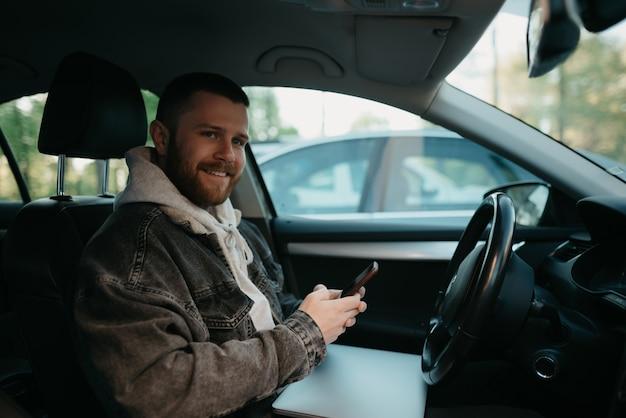彼のラップトップと彼のスマートフォンをコンフォートカーの中に持っている若いひげを生やした男