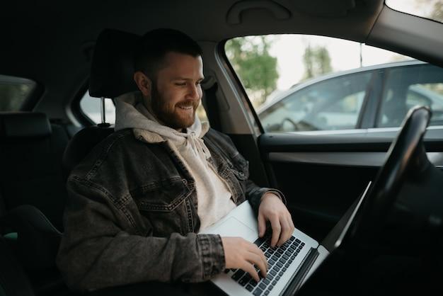 快適な車の中に彼のラップトップを持つ若いひげを生やした男