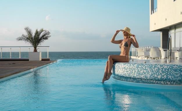 Молодая красивая и сексуальная женщина сидит на краю бассейна. на голову надевается шапка.