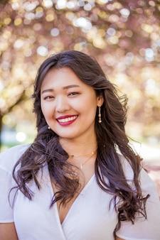 Молодая красивая азиатская женщина в белом платье гуляет в цветущем парке. сакура. цветущие деревья. весна.