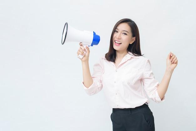 Молодая красивая азиатская женщина объявляет в мегафон на белом фоне