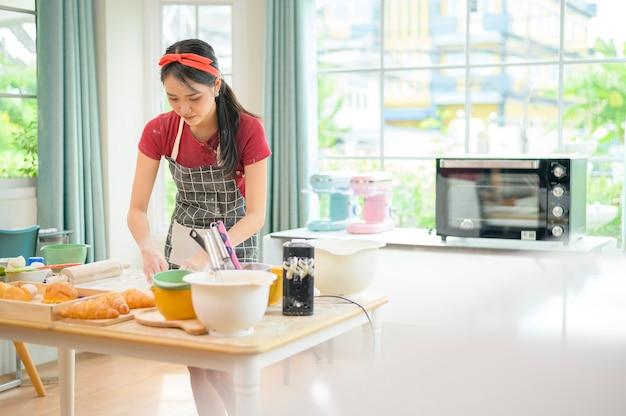 Молодая красивая азиатская женщина выпекает в своей кухне, пекарне и кафе