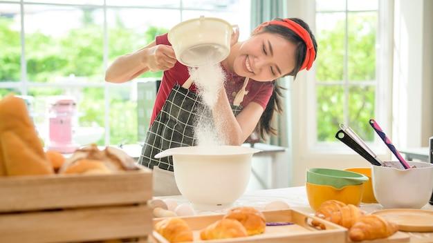 젊은 아름다운 아시아 여성이 부엌, 빵집, 커피숍 사업에서 베이킹을 하고 있습니다