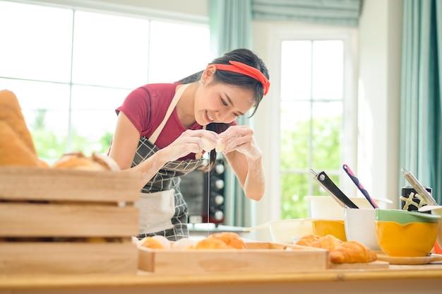 若い美しいアジアの女性が彼女のキッチン、パン屋、コーヒーショップのビジネスで焼いています