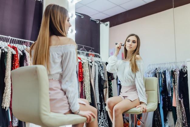 아름다운 금발 소녀가 거울 앞에서 화장을 한다