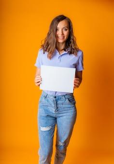 파란색 티셔츠와 청바지를 입은 젊고 아름다운 금발이 손에 흰 종이를 들고 있습니다. 복사 공간입니다.