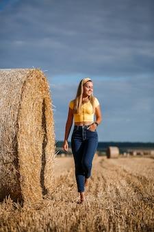 젊고 아름다운 금발이 거대한 건초 뭉치 근처의 깎은 밀밭에 서서 자연을 즐기고 있습니다. 마을의 자연