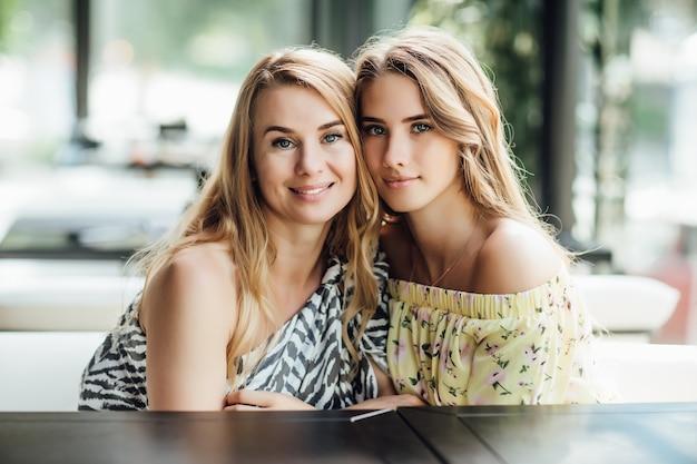 若い美しいブロンドの女性と彼女のお母さんは夏のテラスカフェで休む