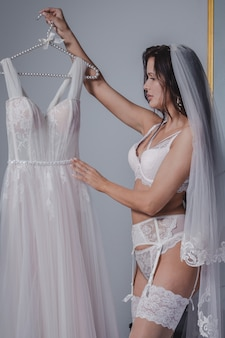 Молодая красивая невеста в нижнем белье смотрит на свое свадебное платье в отеле