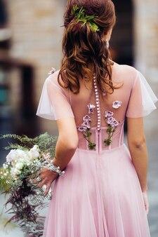 젊은 아름 다운 신부 이탈리아 피렌체의 구시 가지의 중심에 선다. tuscany.italy에서 부케와 함께 아름 다운 핑크 드레스의 신부.