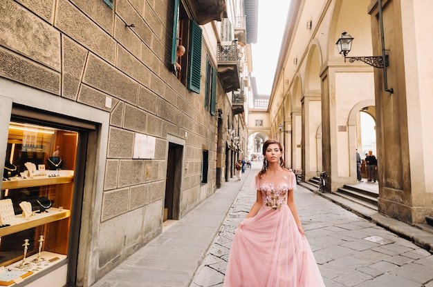若い美しい花嫁は、イタリアのフィレンツェの旧市街の中心に立っています。