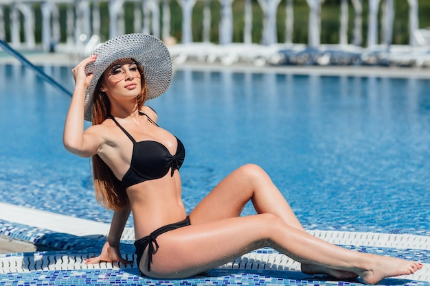 Молодая красивая шатенка в черном купальнике, солнцезащитные очки у бассейна у воды