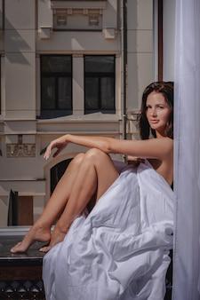 창에 담요에 앉아 호텔에서 젊은 아름 다운 갈색 머리 소녀