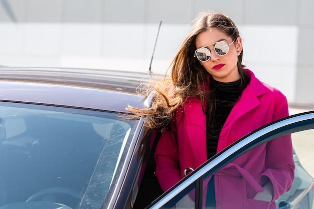 若い美しいビジネス女性が車から降りる