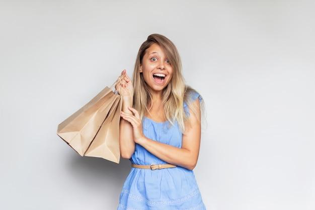 Молодая красивая кавказская улыбающаяся блондинка в синем платье держит в руке бумажные эко-пакеты