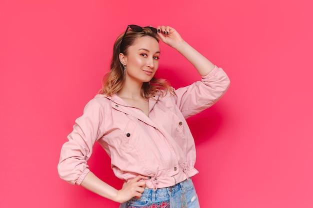 Молодая красивая уверенная в себе шатенка в повседневной стильной куртке и джинсовых шортах позирует с солнцезащитными очками на голове, изолированной на ярко-розовой стене