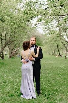若い美しいカップル、薄紫色のドレスを着た女の子、リンゴの木のある夏の公園の黒人男性1