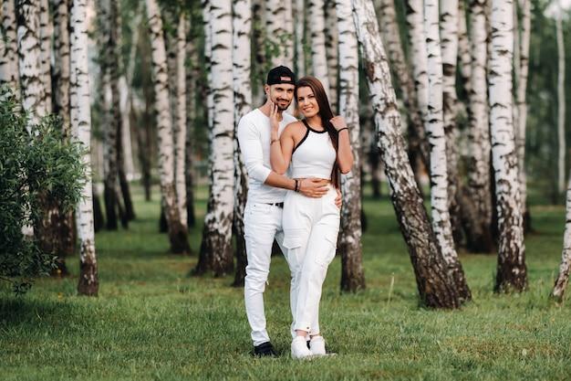 白樺の木立を背景に白い服を着た若い美しいカップル。自然の公園で恋をしている人々の肖像画。