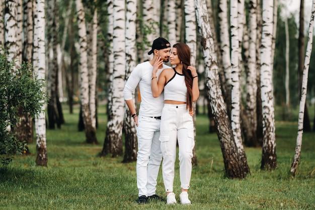 자작 나무 숲의 배경에 흰색 옷을 입고 젊은 아름다운 부부