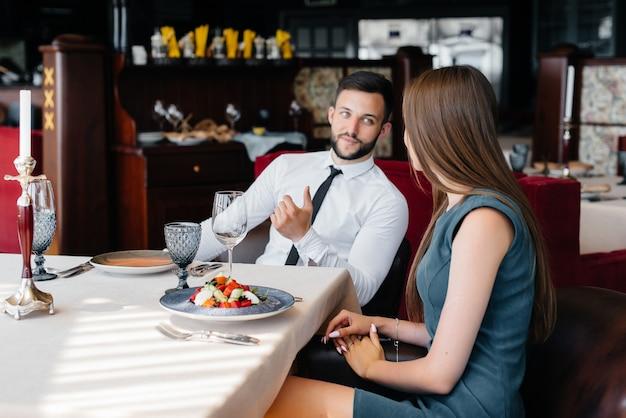 아름다운 젊은 부부가 고급 레스토랑에서 점심을 먹고 있습니다. 케이터링에서 고객 서비스.