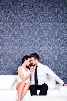 ソファの上の若い美しいカップル。