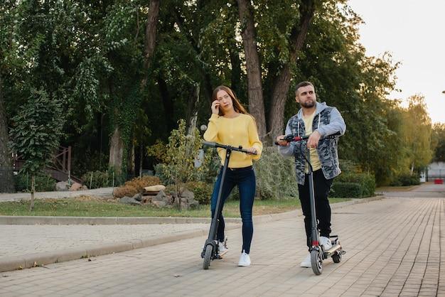 따뜻한 가을 날 공원에서 젊은 아름다운 부부가 전기 스쿠터를 타고
