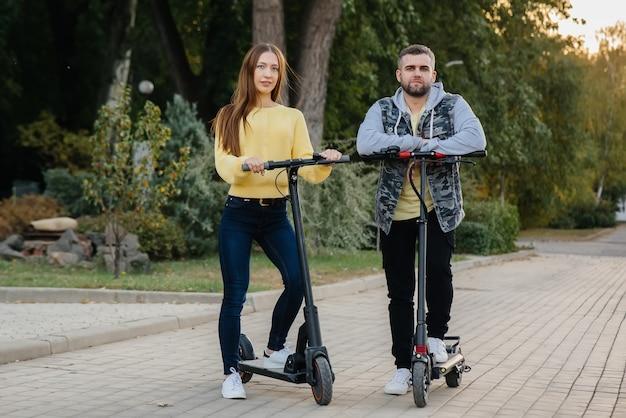 Молодая красивая пара катается на электросамокатах в парке в теплый осенний день