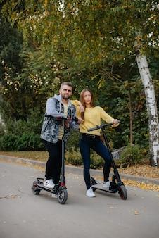 若い美しいカップルが暖かい秋の日に公園で電動スクーターに乗る